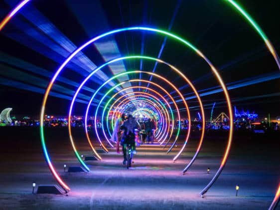 People walking under a multi-coloured light installation